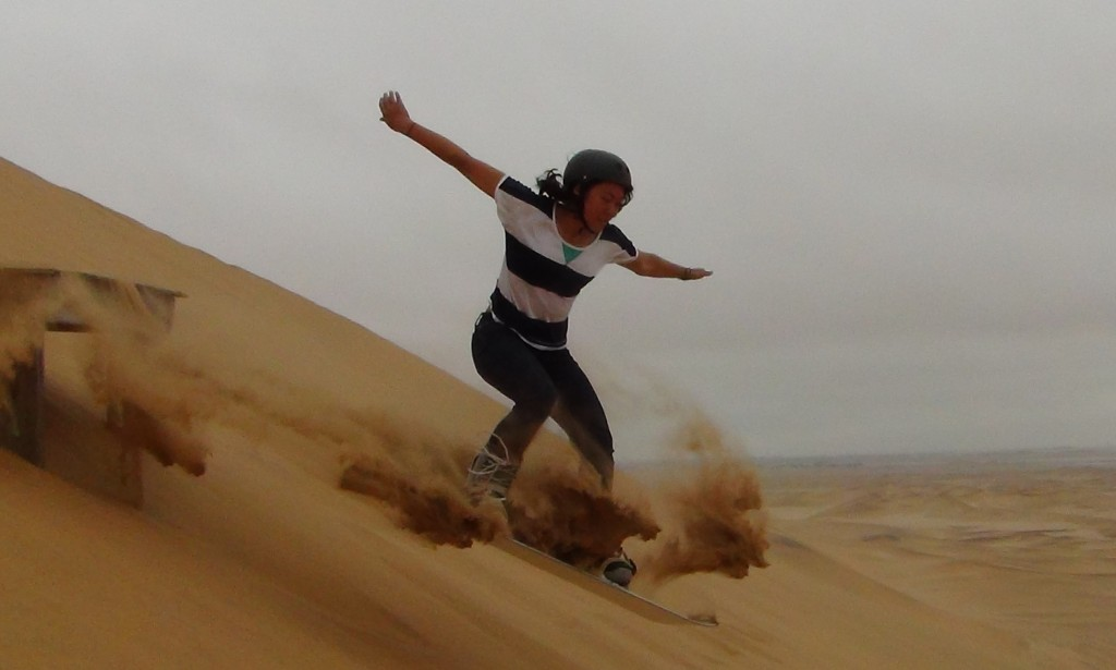 Lis attempts a jump while sandboarding